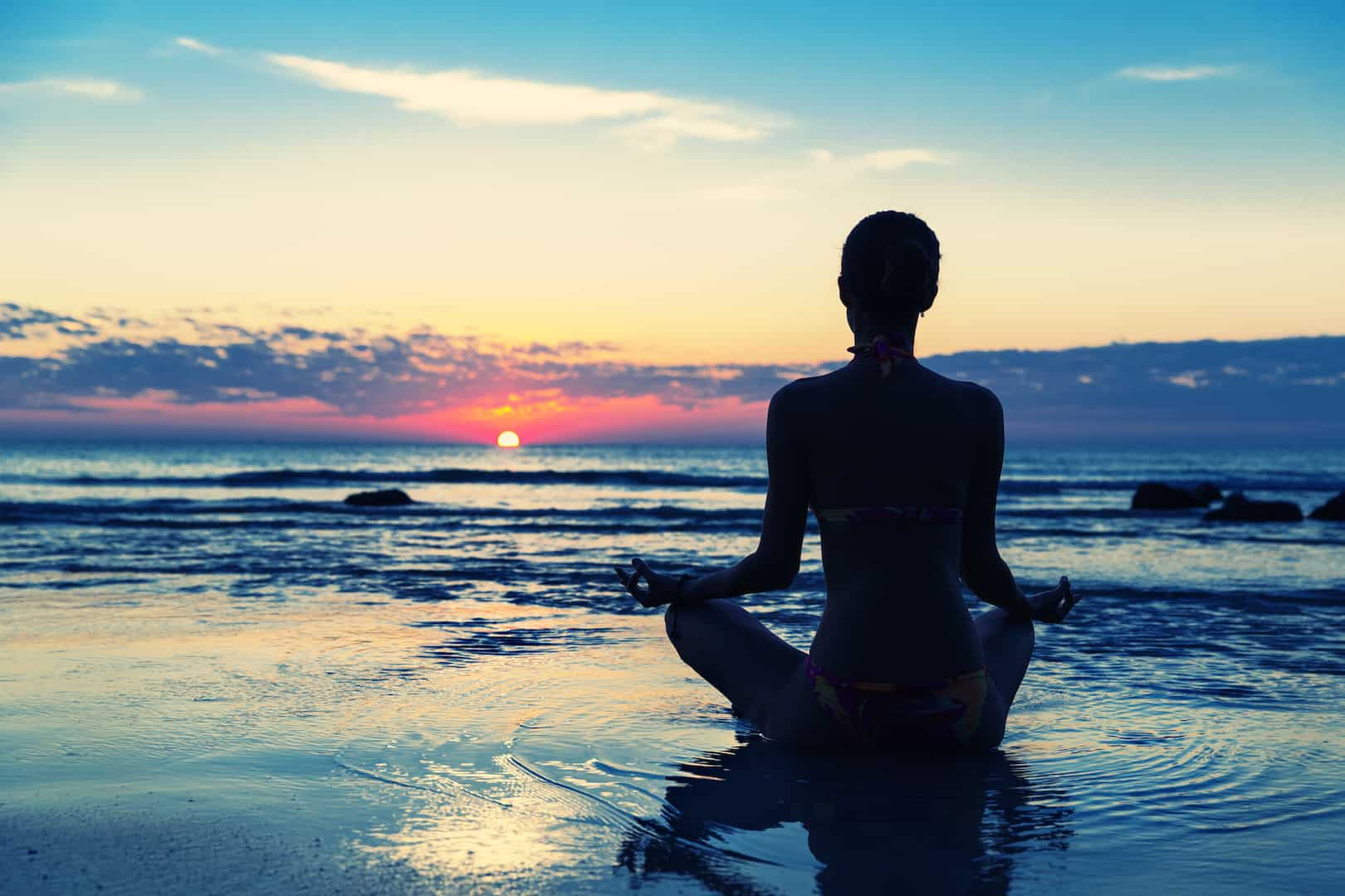 Meditation on the beach. Women sitting in lotus, likes to do acupressure