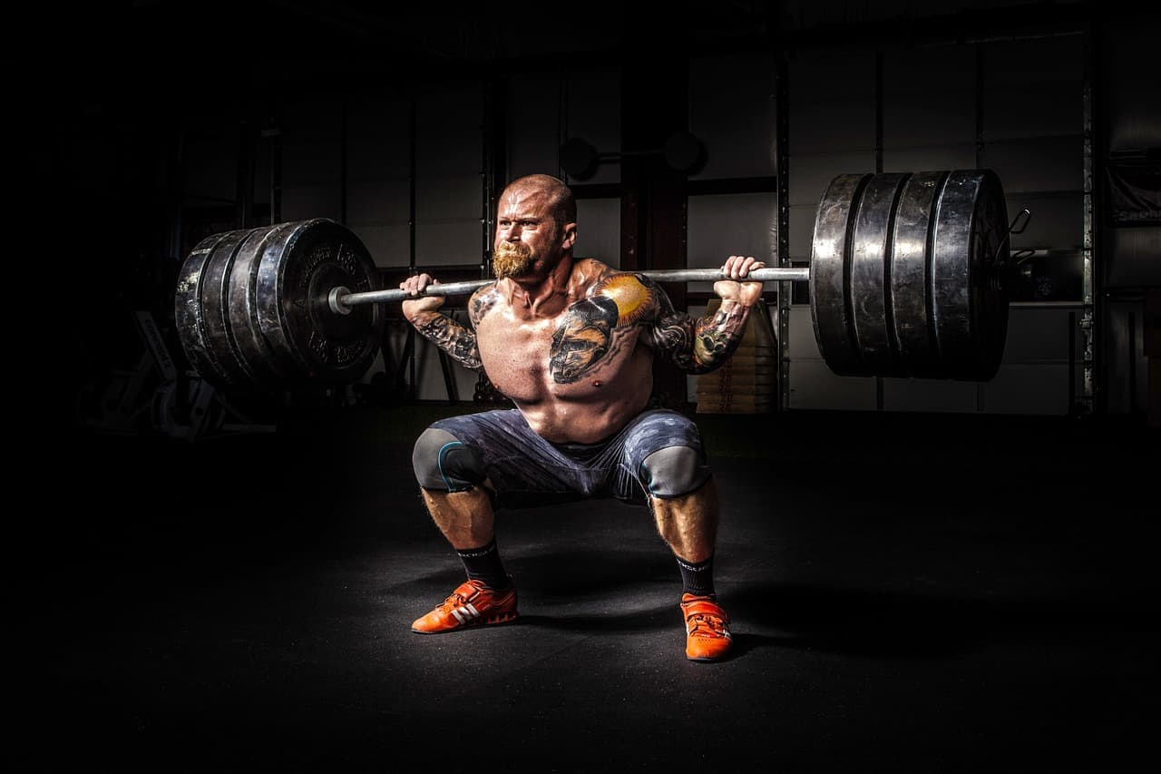 Powerlifter doing squats with a high weight, developing muscle
